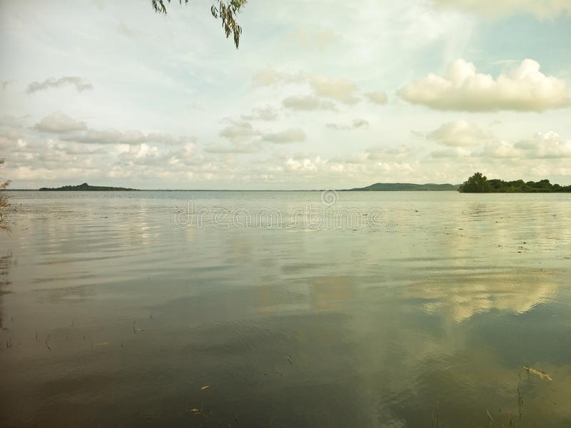 Lake in the evening. A lake is an area filled with water, localized in a basin, that is surrounded by land, apart from any river or other outlet that serves to stock image