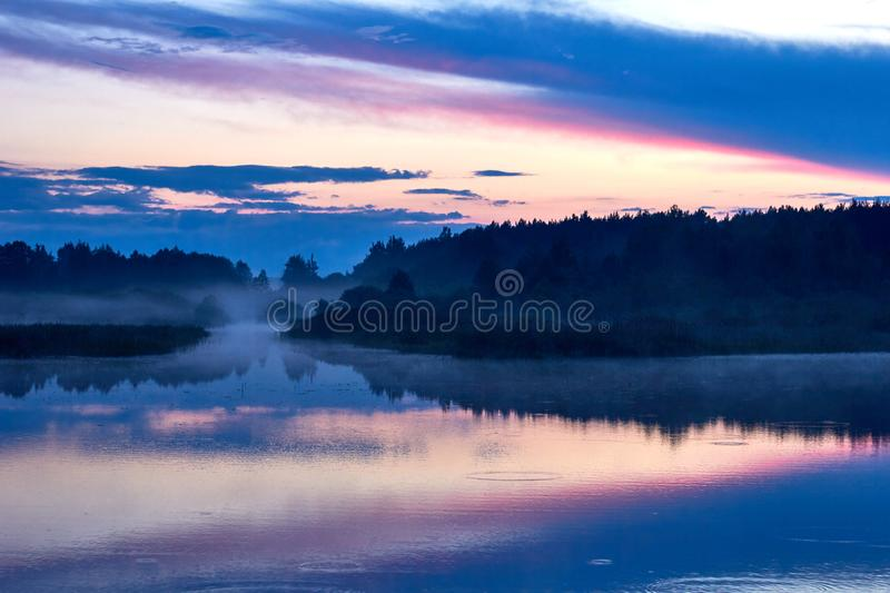 Lake and forest in a fog, landscape of wild nature at sunset stock photo