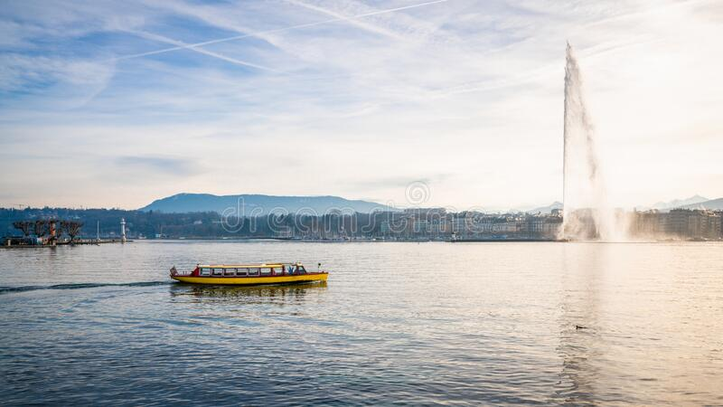 Lake Geneva panorama with the famous Jet d'Eau or water jet and small yellow shuttle boat Geneva Switzerland. Lake Geneva panorama with the famous Jet d&# stock photo