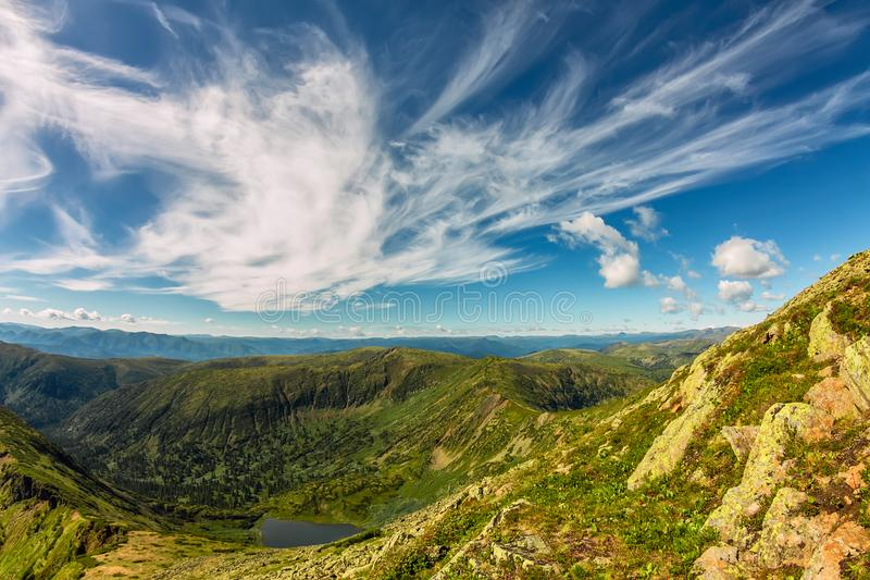 Lake in green mountains with feathery clouds, summer landscape royalty free stock photo