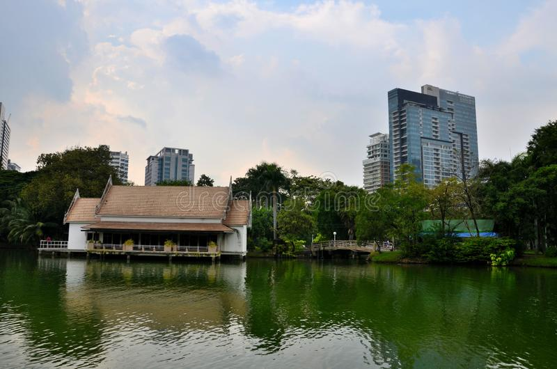 Lake and house with skyline at Lumphini Park Bangkok Thailand. Bangkok, Thailand - November 16, 2018: A lake with a lakeside building and a water mill located stock image