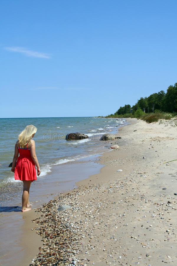 Lake Huron Beach Area. A young girl walks along the beach on the coast of Lake Huron, one of the Great Lakes in the United States royalty free stock photography