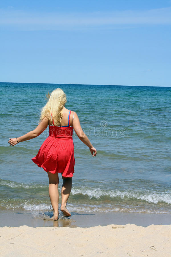 Lake Huron Beach Area. A young girl walks into the water on the coast of Lake Huron, one of the Great Lakes in the United States stock image
