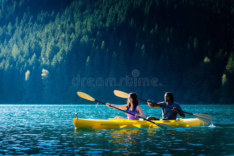 Lake Kayaking Couple. Couple paddling in kayak on lake