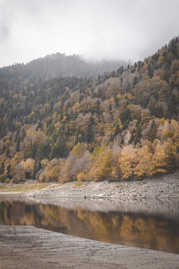 Lake Kruth-Wildestein in Vosges with low waterlevel and autumnal trees on mountains. dark moody skies royalty free stock photography