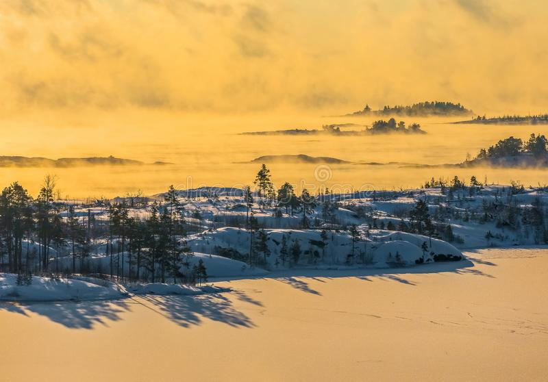 Lake Ladoga i förkylningen övervintrar trees för snow för sky för lies för frost för mörk dag för bluefilialer Dimma på solnedgån arkivbild