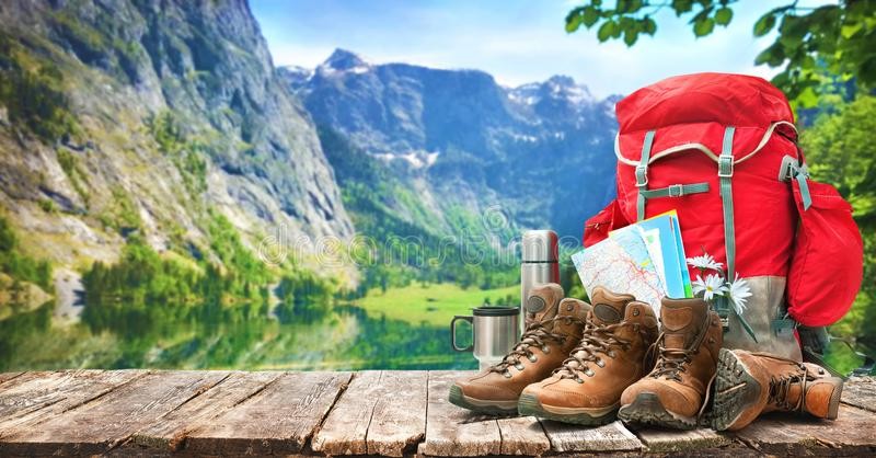 Lake landscape with big backpack and trekking boots. In mountains royalty free stock photography