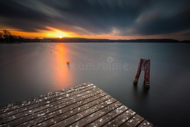 Lake landscape with jetty. Long time exposure. Beautiful lake landscape with jetty. Long time exposure photo with filter. Polish lake shore at cloudy weather stock image