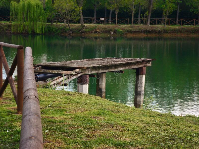A natural park to Agliana. Lake located in a natural park in the town of Agliana in Tuscany, Italy with an old jetty royalty free stock image