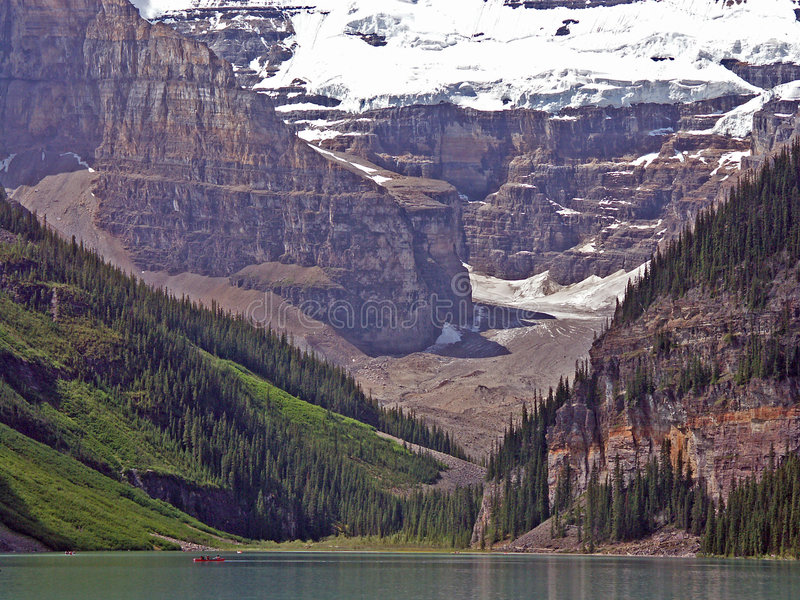 Lake Louise. A view of Victoria glacier over Lake Louise, with a red canoe royalty free stock image