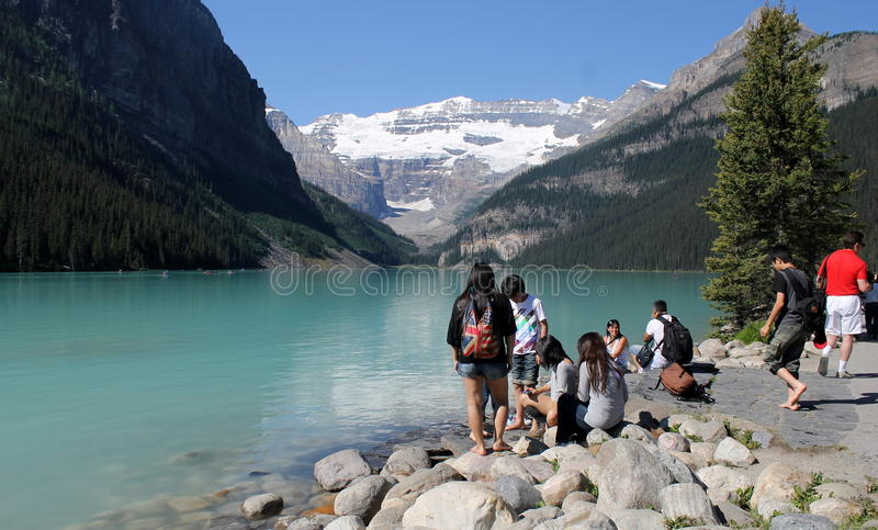Lake Louise, Canada. Hikers and visitors on rocky shore of Lake Louise, Alberta, Canada, mountainous background stock photo