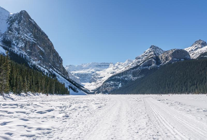Lake Louise, CANADA - MARCH 20, 2019: frozen lake and mountains with snow peaks. Winter, ice, cold, landscape, nature, beautiful, tourism, travel, north, sun royalty free stock photos