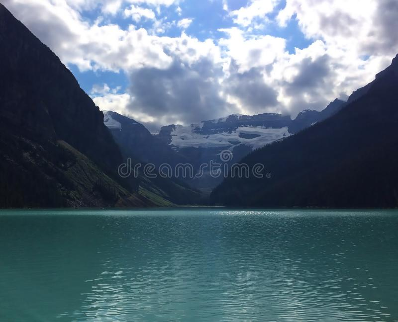 Emerald waters of Lake Louise. Lake Louise, named Lake of the Little Fishes by the Stoney Nakota First Nations people, is a glacial lake within Banff National royalty free stock photography