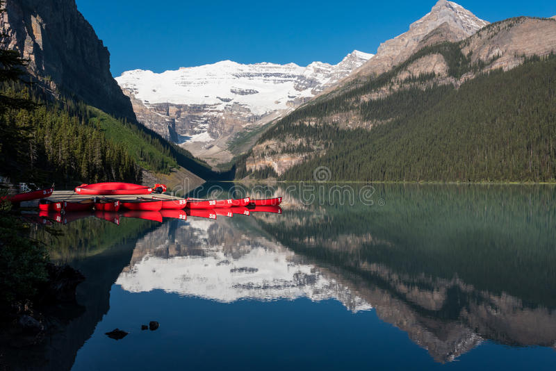 Lake Louise and Red Canoes. With mountain reflection royalty free stock images