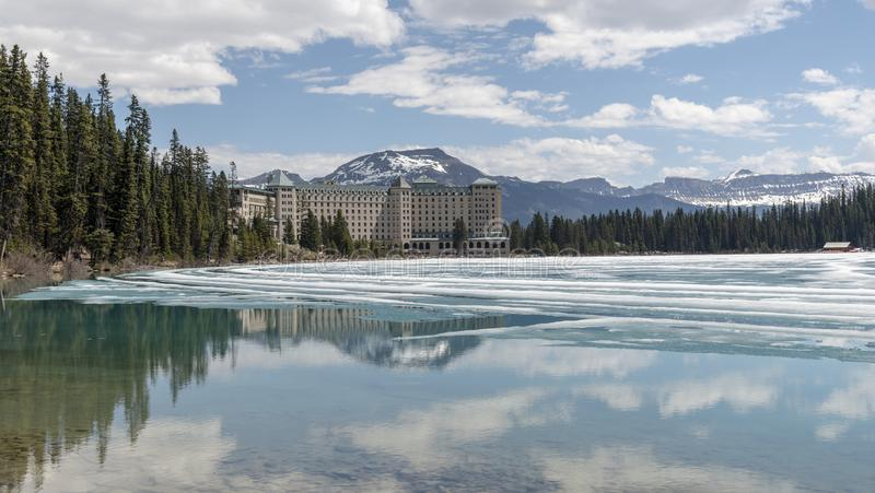 Lake Louise showing the impressive Fairmont Hotel. Fairmont Hotel overlooking the thawing Lake Louise in the Banff National Park stock photo