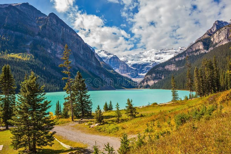 Lake Louise is surrounded by mountain and glaciers. Magnificent Lake Louise is surrounded by mountain peaks and glaciers. Great sunny day. Rocky Mountains royalty free stock photo