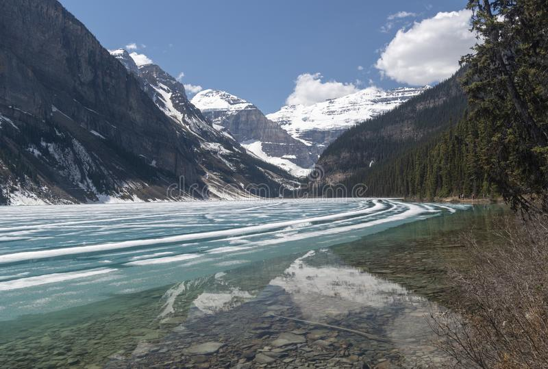 Lake Louise towards Victoria mountain. Thawing Lake Louise in the Banff National Park looking towards Victoria Mountain stock photography