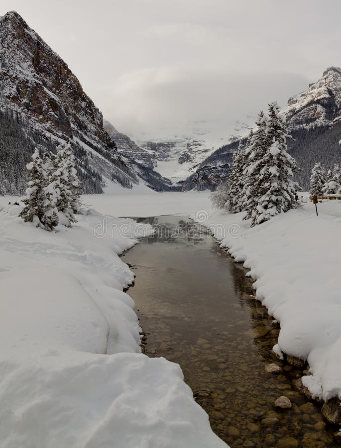 Lake Louise. View of the glacier from across a frozen lake Louise covered in snow royalty free stock images