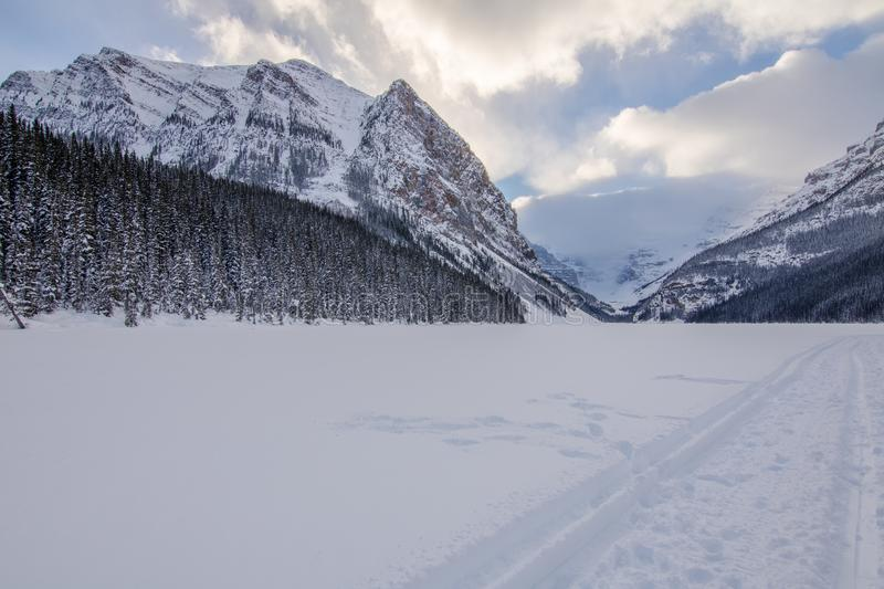 Lake Louise Winter. Winter time at Lake Louise Alberta, Canada. Ice and snow covered lake with mountains in the background and a cloudy sky overhead. Photo royalty free stock photos