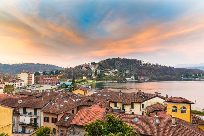 Lake Maggiore, Laveno, Italy. Picturesque sunrise. View towards the lake Maggiore, the pier of the ferry, the railway station and the lake promenade of Laveno royalty free stock photography
