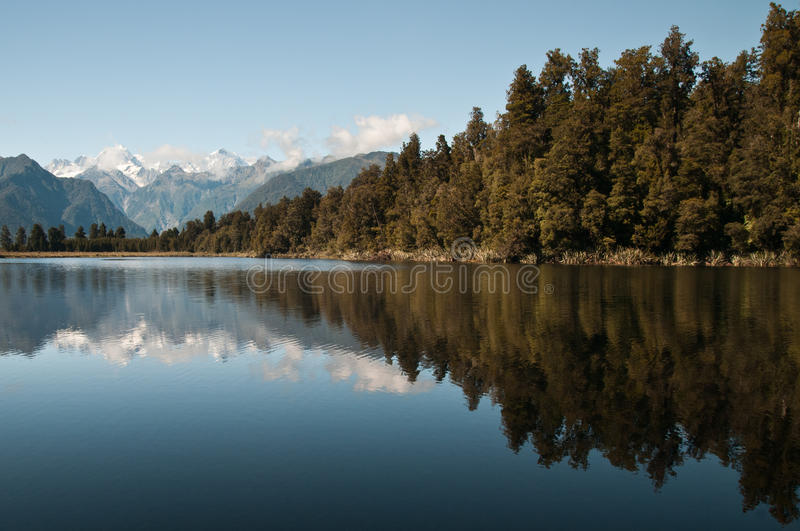 Lake matheson, NZ. Lake Matheson, New Zealand, is also called mirror lake, for its perfect reflections. Far away lies mt Cook royalty free stock photo