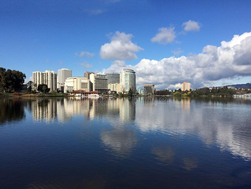 Lake Merritt, Oakland, California. Office buildings reflected in water with big puffy white clouds stock photography