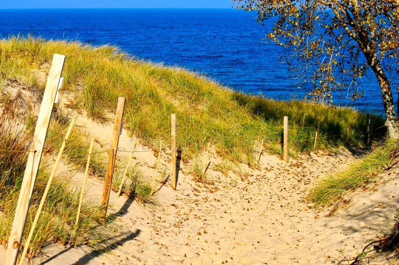 Lake Michigan during Autumn in Indiana Dunes. Sandy path on a sand dune in the Indiana Dunes national forest, with footprints in the sand going down a hilly stock image