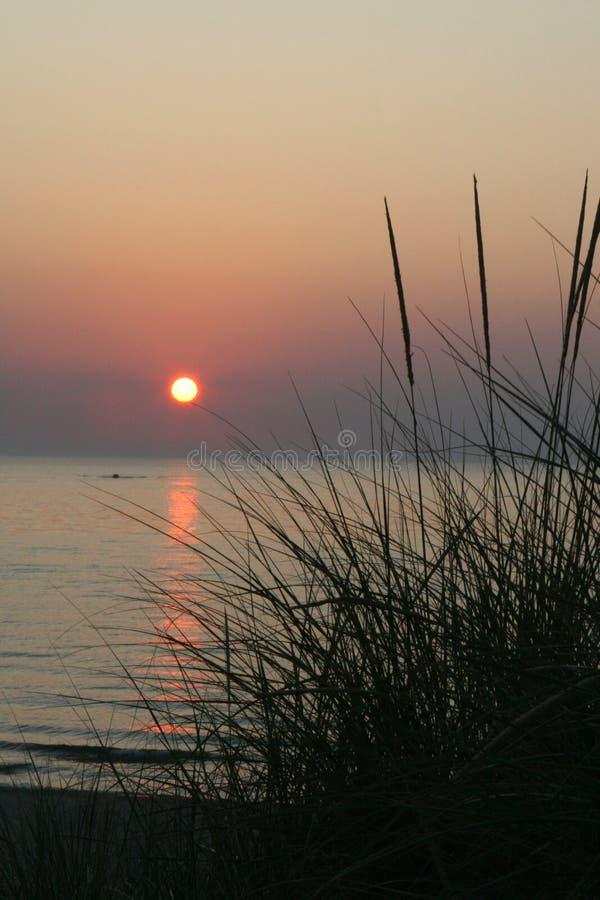 Lake Michigan Sunset. Summer sunset on great Lake michigan setting sun sawgrass beach water reflection watersport stock photography