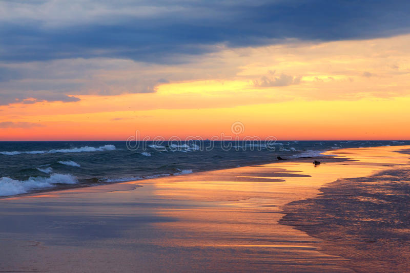 Lake Michigan Sunset and Beach Reflections. As the sun slips from the sky and into Lake Michigan it skims its light beams across the surface of the sand like a royalty free stock photos
