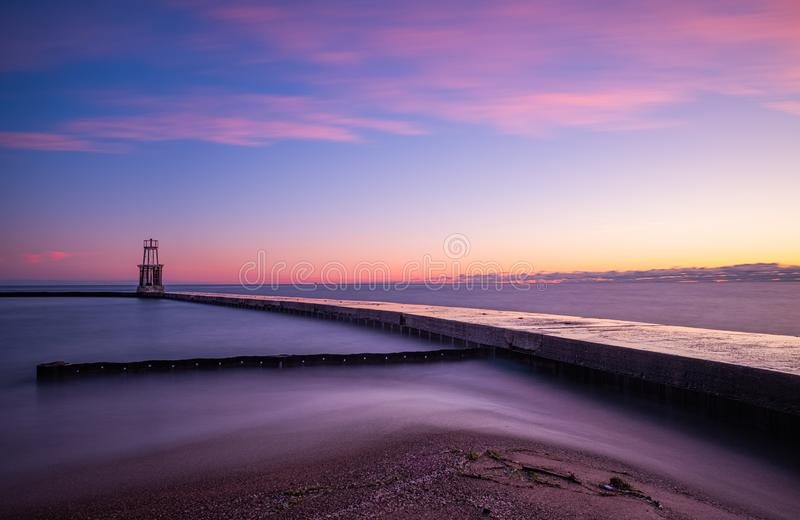 Lake Michigan water pours over walkway. Near Chicago, Illinois. Pink morning sunrise overhead stock photo