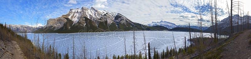 Lake Minnewanka Early Springtime Hiking Canadian Rocky Mountains Banff National Park. Wide Panoramic Landscape of Frozen Lake Minnewanka and Snowcapped Mountain stock image