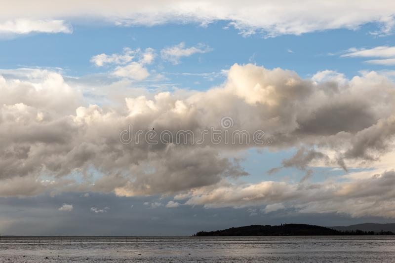 Lake on moody day with big clouds over an island and blue sky royalty free stock image