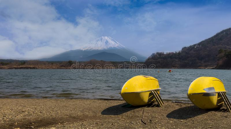 Lake Motosu, a green lake with two yellow kayaks on the shore royalty free stock image