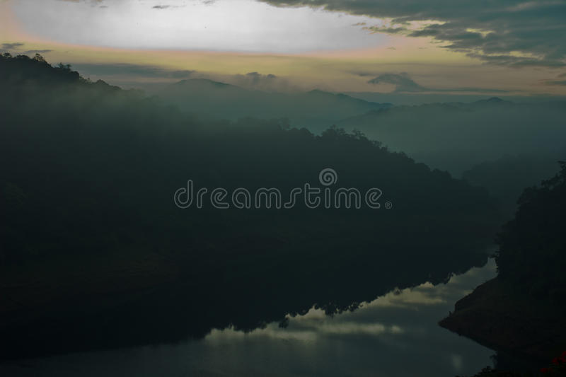 Lake and mountains in moody morning. Early morning shot of a forest landscape in moody morning. Reflections of the cloud pattern can be seen in the calm lake royalty free stock photo