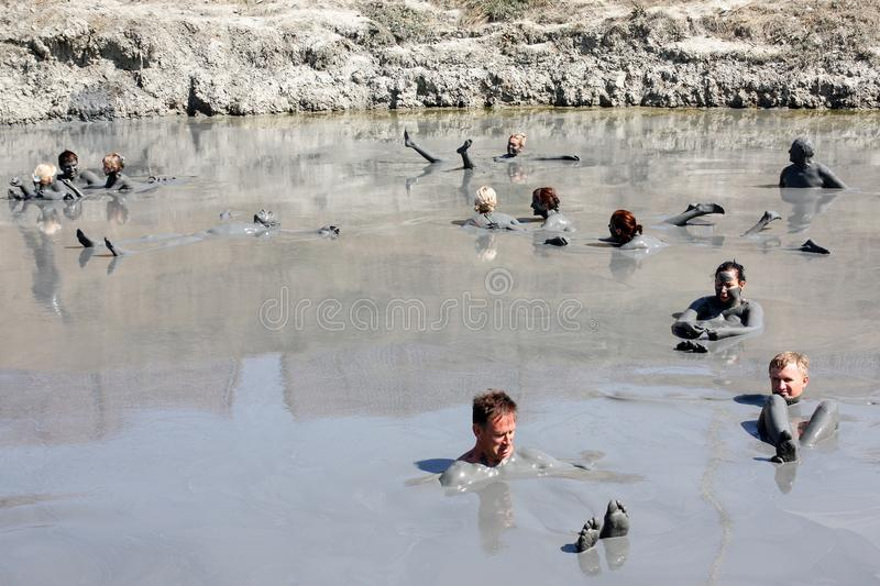 Treatment with volcanic mud. People smear the body with mud and bathe in the healing lake. Lake with mud, curative mud, volcanic mud, people in mud, mud royalty free stock photo