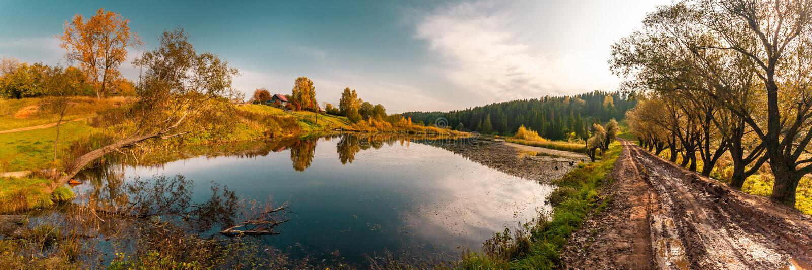 The lake near the village, with reflection of sky, trees and houses on a water smooth surface, a panorama from several frames royalty free stock photos