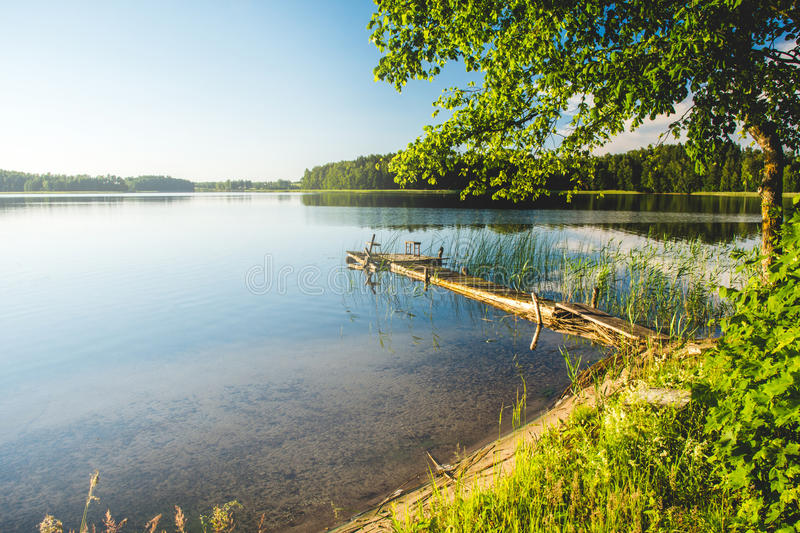 Lake with pier in forest royalty free stock photo