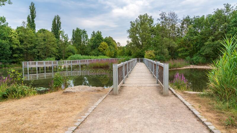 Nordsternpark in Gelsenkirchen, North Rhine-Westfalia, Germany. A lake with a pier leading into it, seen at the Nordsternpark, Gelsenkirchen, North Rhine royalty free stock image