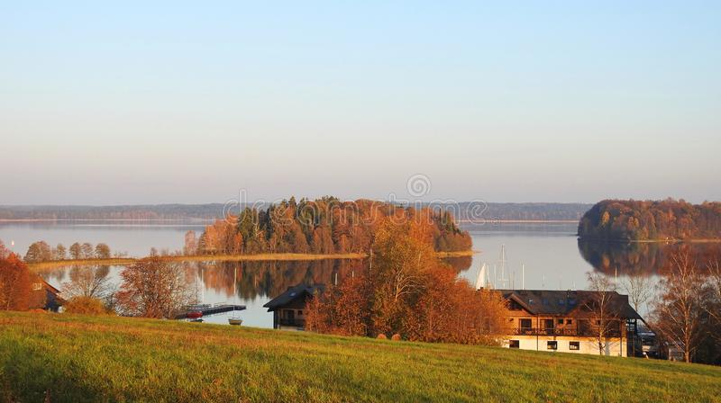 Lake, homes and beautiful plants, Lithuania. Lake Plateliu, homes, beautiful trees and reed plants in autumn stock images