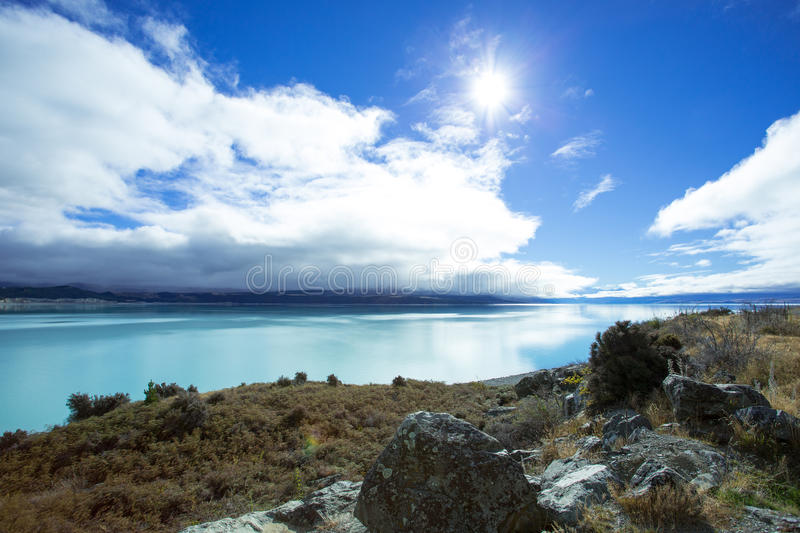 Lake Pukaki On A Shiny Day. Lake Pukaki is fed from melting of the Tasman and Glaciers. The Lake has a distinctive blue color, that is caused by glacial flour stock image