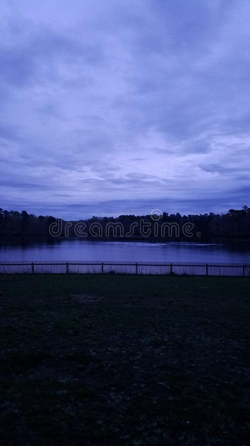 Lake in Purple Hues. Grass, colors, trees royalty free stock photo