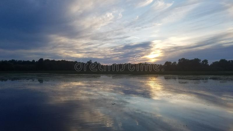 Lake reflections. Clouds reflect off the river like a mirror royalty free stock images