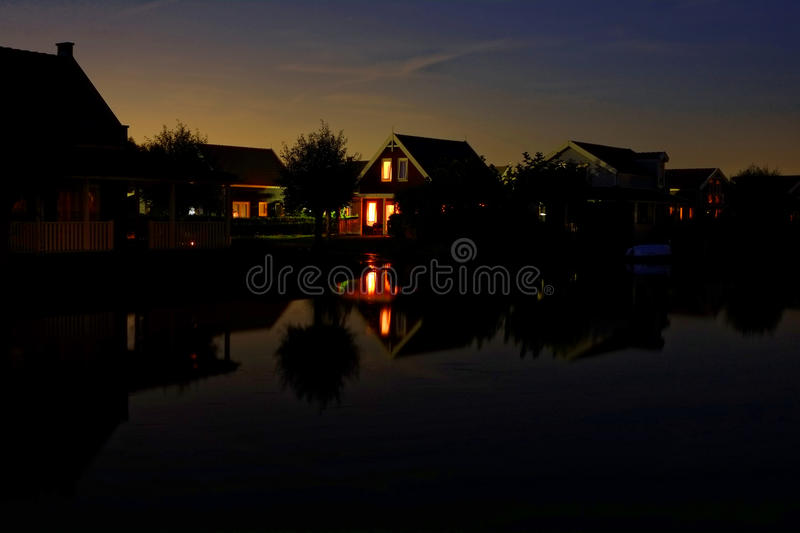 Lake resort scene at dusk with lights on in homes royalty free stock photo