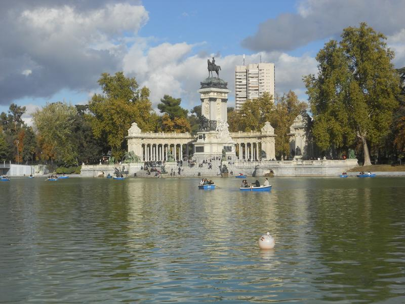 Lake in retiro park in madrid with statues, water, and rowing boats royalty free stock images