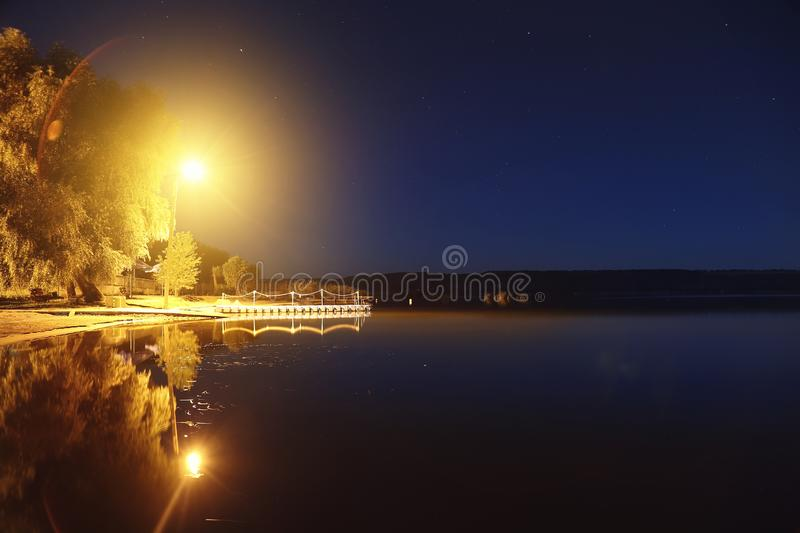 Lake or river sand shore with trees and glowing lantern over pantoon pier and dark blue starry sky on background. Tranquil nature stock images