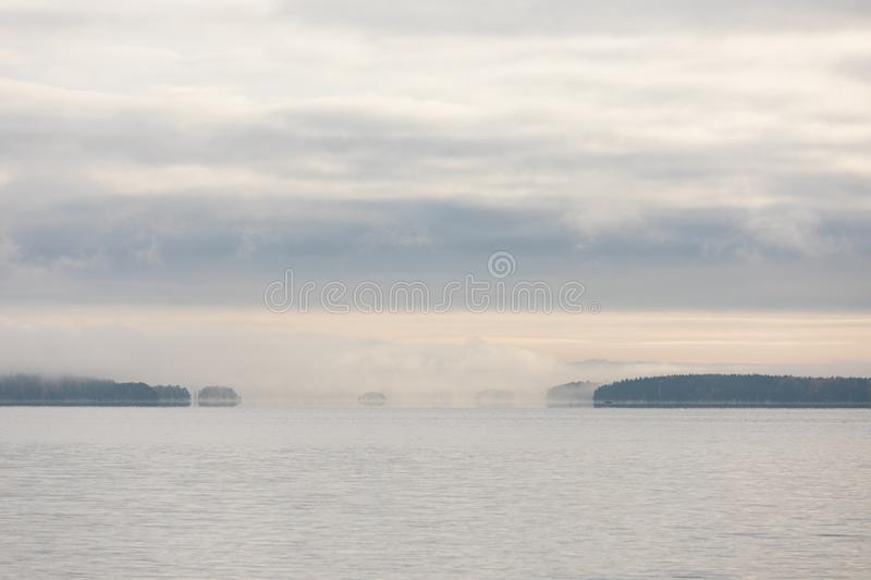 Lake scape and opposite shore forest at dawn. Lake scape and foggy opposite shore forest at dawn royalty free stock photo