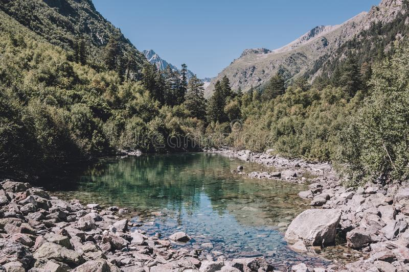 Lake scenes in mountains, national park Dombai, Caucasus, Russia, Europe. Sunshine weather, blue color sky, far away green trees. Colorful summer day, time royalty free stock photography