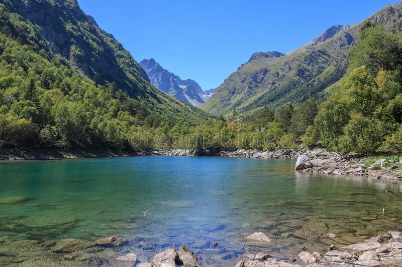 Lake scenes in mountains, national park Dombai, Caucasus, Russia, Europe. Sunshine weather, blue color sky, far away green trees. Colorful summer day, time royalty free stock photos