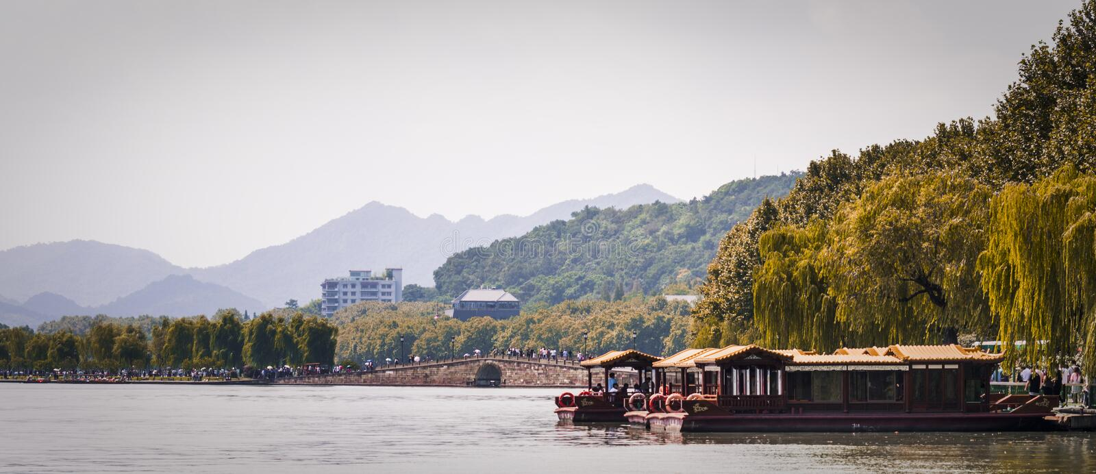 Lake Scenic Views. A picture of Hangzhou& x27;s beautiful lake as the sun begins to drop. Green trees are placed at the side with the main image focused on the stock photos
