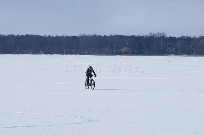 Unidentified male cyclist riding a bike in the winter on the frozen lake stock photo